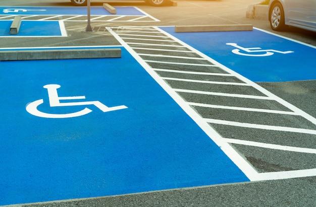 Asfaltowy parking dla niepełnosprawnych kierowców w supermarkecie lub centrum handlowym. miejsce parkingowe dla osób niepełnosprawnych. farba znak wózka inwalidzkiego na parkingu asfaltowym. parking dla niepełnosprawnych.