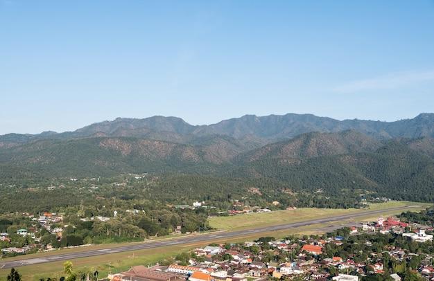 Asfaltowy pas startowy małego lotniska w dolinie.