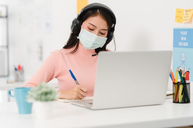 Asia businesswoman dystans społeczny w nowej normalnej sytuacji w celu zapobiegania wirusom podczas prezentacji laptopa kolegom na temat planu w rozmowie wideo podczas pracy w biurze. życie po wirusie koronowym.