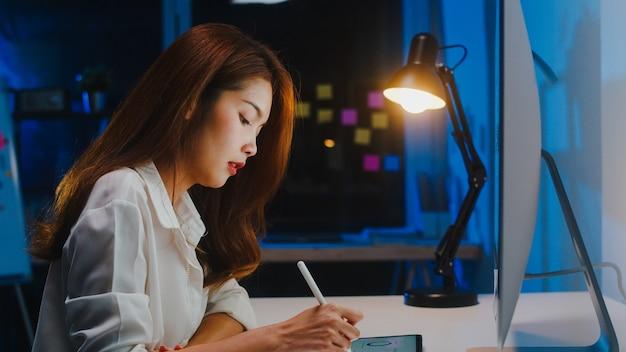 Asia businesswoman rozmawia z kolegami na komputerze o planie w rozmowie wideo podczas pracy w domu w salonie w nocy. samoizolacja, dystans społeczny, kwarantanna w celu zapobiegania koronawirusowi.