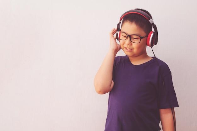 Asia chłopiec słucha muzykę z hełmofonami.