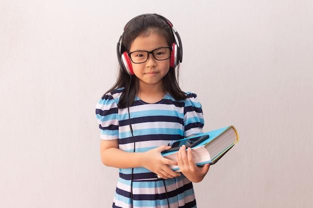Asia dziewczyna słucha muzykę i trzyma książki z hełmofonami