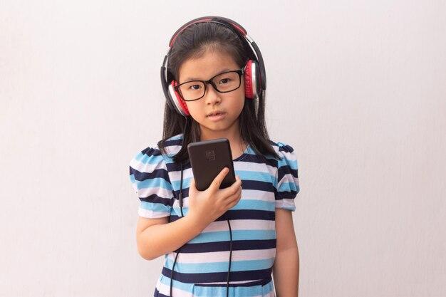 Asia dziewczyna słucha muzykę z hełmofonami