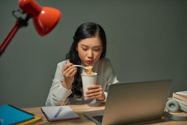 Asia freelance smart business women jedzące makaron instant podczas pracy na laptopie w salonie w domu w nocy
