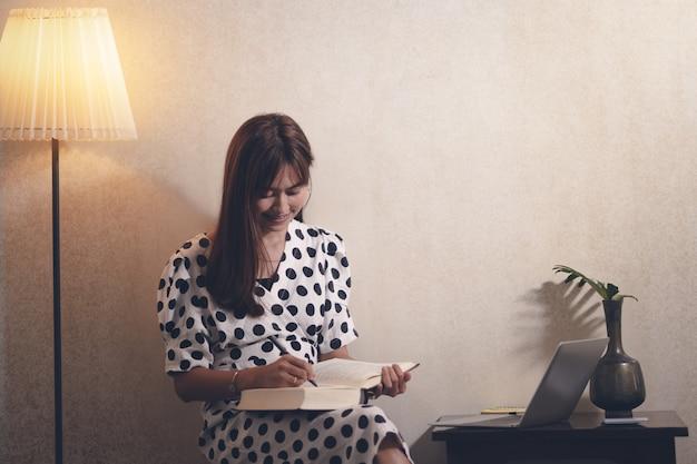Asia kobieta czytająca książkę w wolnym czasie z radością