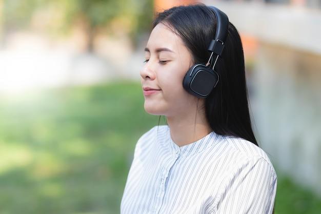 Asia kobieta słucha muzyki z relaksem i szczęśliwa na wakacjach.