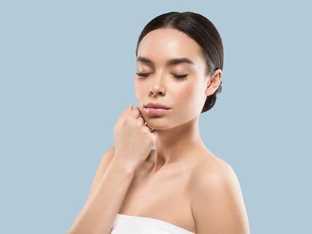 Asia kobieta uroda twarz ciała portret dotykając jej twarzy zdrowej skóry. kolor tła. niebieski