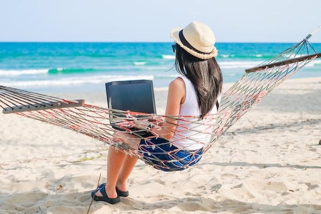 Asia kobiety obsiadanie na hamaku blisko plaży i używać laptop dla jej pracy i sprawdzać biznes podczas jej wakacji.