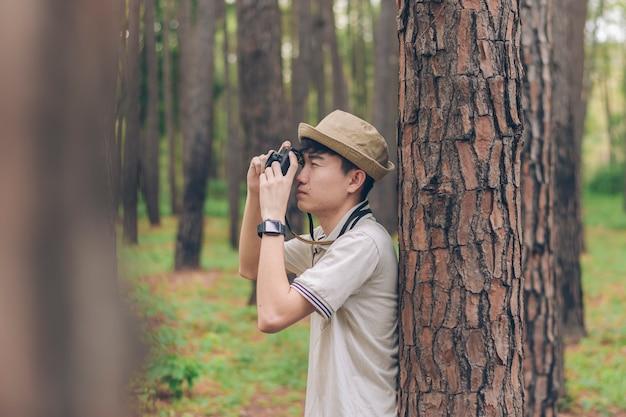 Asia ma na sobie koszulę, a kapelusz stoi na drzewie i robi zdjęcia w lesie
