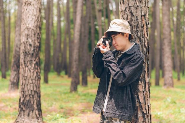 Asia ma na sobie koszulę i dżinsową kurtkę, a kapelusz stoi na drzewie i robi zdjęcia w lesie