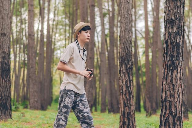 Asia ma na sobie koszulę, kapelusz i spodnie w kamuflażu, spaceruje i robi zdjęcia w lesie