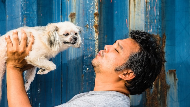 Asia mężczyzna i psi szczęśliwy przytulenie z zbiornikiem