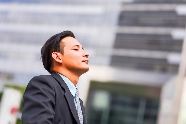 Asia młody biznesowy mężczyzna przed nowożytnym budynkiem w śródmieściu