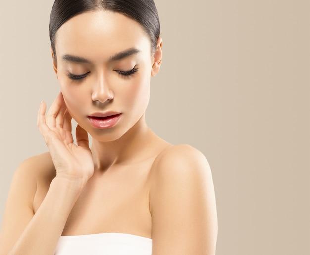 Asia piękna kobieta z zamkniętymi oczami zdrowa skóra twarzy czysta świeża skóra spa. strzał studio. kolor tła.