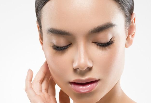 Asia piękna kobieta z zamkniętymi oczami zdrowa skóra twarzy czysta świeża skóra spa. strzał studio. na białym tle.