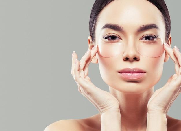 Asia piękna kobieta zdrowa skóra twarzy czysta świeża skóra spa. strzał studio. kolor tła.