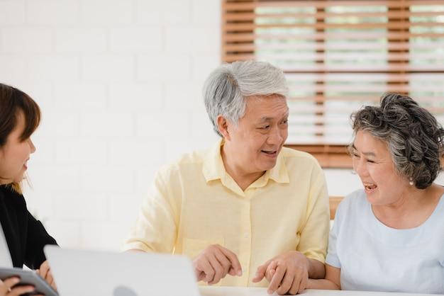 Asia smart female agent oferuje ubezpieczenie zdrowotne dla starszych par według dokumentów, tabletów i laptopów.