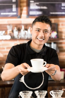 Asian barista oferuje filiżankę kawy parzonej