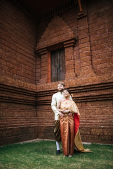 Asian bride and caucasian groom mają romantyczny czas z tajlandii sukienka