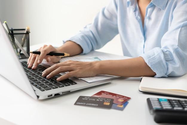 Asian businesswoman pracy na komputerze przenośnym w biurze. kobieta sprawdzanie salda konta i obliczanie kosztów karty kredytowej. wydatki rodzinne, koncepcja biznesu i finansów. ścieśniać.