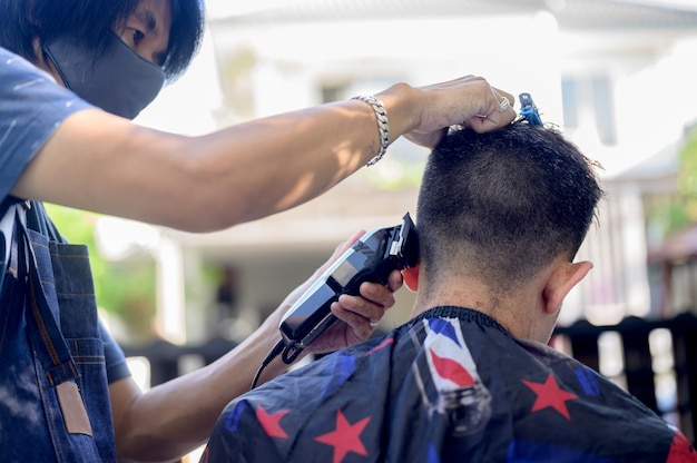 Asian co strzyżenie w ogrodzie domu. nauka kursów fryzjerskich online podczas blokady dla nowego zawodu. nowe normalne życie po pandemii epidemii covid-19.