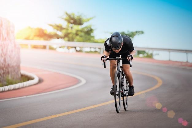 Asian człowiek kolarstwo odkryty ćwiczenia rower ścieżki w godzinach porannych.