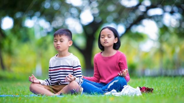Asian dzieci robi joga poza w parku na świeżym powietrzu