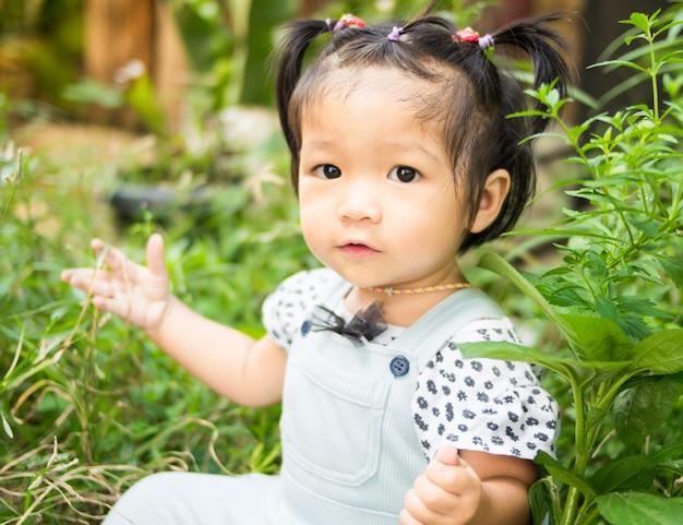 Asian dziewczynka siedzi w zielonym parku