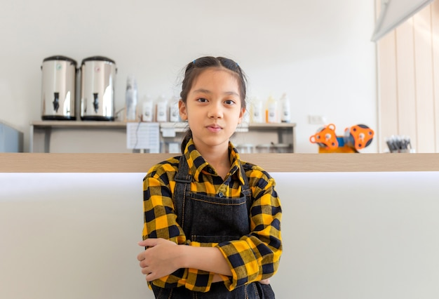 Asian dziewczynka ubrana w fartuch szczęśliwa buźka uśmiecha się ze skrzyżowanymi rękami patrząc w kamerę