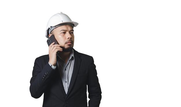 Asian engineering człowiek ubrany hardhat rozmawia telefon komórkowy na białym tle, ścieżkę przycinającą.