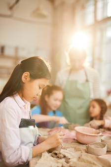 Asian girl shaping clay