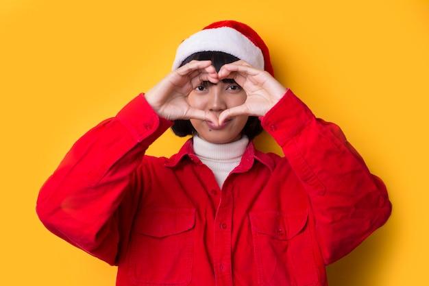 Asian girl ubrana w santa hat gestem miłości bożego narodzenia