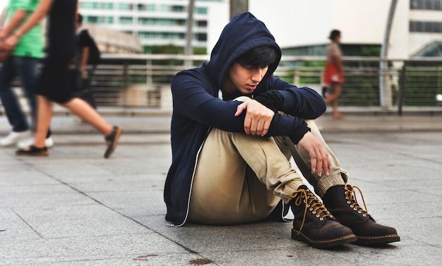 Asian guy usiądź na depresji ulicznej