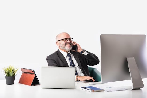 Asian indian starszy finansowy biznesmen siedzi przy swoim stanowisku pracy lub biurku przed komputerem, laptopem i tabletem. rozmawianie przez telefon podczas robienia formalności