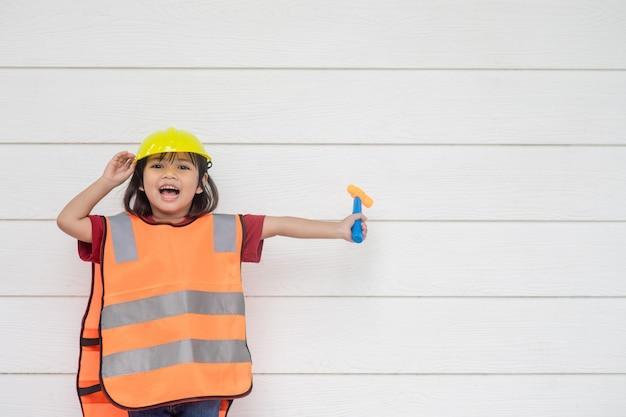 Asian kid dziewczyna nosi odblaskowe koszule i żółty kapelusz. aby uczyć się i wspomagać rozwój,
