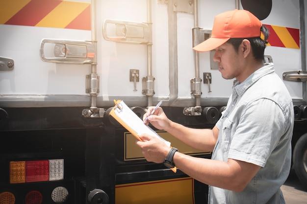 Asian kierowca ciężarówki trzyma schowek jego sprawdzanie bezpieczeństwa stalowe drzwi ciężarówki kontenera.