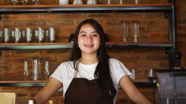 Asian kobieta barista smilling patrzeć na kamerę w kawiarni