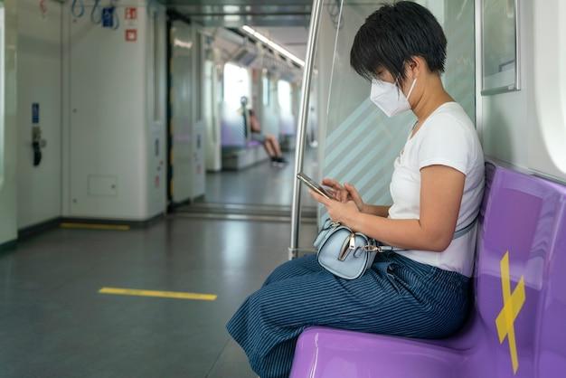 Asian kobieta kobieta siedzi w odległości metra na jedno miejsce od innych ludzi