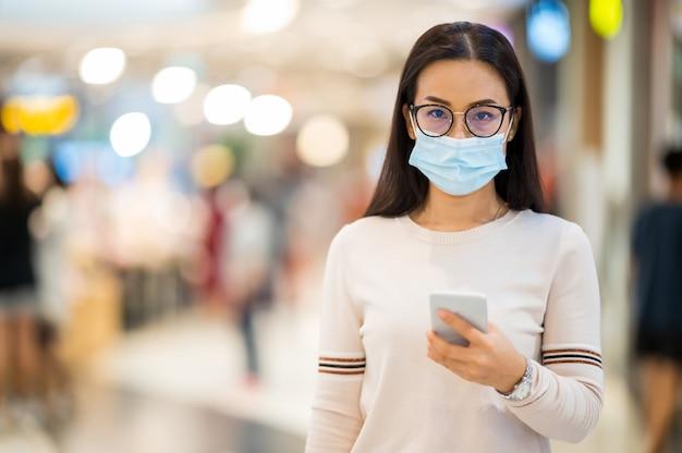 Asian kobieta ma na sobie maskę i trzymaj telefon komórkowy zakupy w sklepie w trakcie