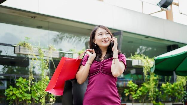 Asian kobieta moda zakupy w centrum handlowym z dzwoniąc do swojego przyjaciela