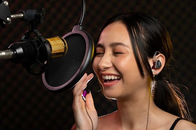 Asian kobieta noszenie słuchawek śpiewa z wiszącym mikrofonem. pokój soundproof.