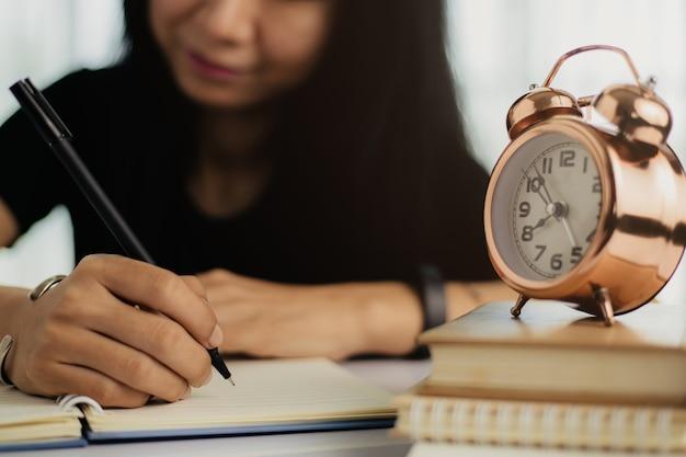 Asian kobieta pisze w zeszycie z budzikiem w książkach