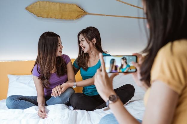 Asian Kobieta Robienie Zdjęć Swoich Przyjaciół Za Pomocą Telefonu Podczas Spędzania Czasu Razem W Sypialni Premium Zdjęcia