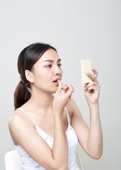 Asian kobieta stosowania szminki w lustrze