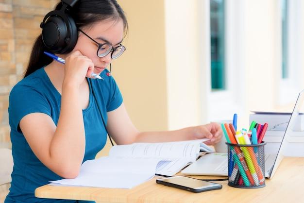 Asian kobieta student nastolatka z okularami słuchawki siedzi patrząc poważny czytanie książki martwić się za pomocą laptopa na stole nauki online badania. edukacja z klasy uniwersyteckiej w domu