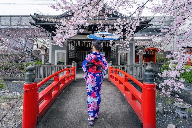 Asian kobieta ubrana w tradycyjne japońskie kimono i kwiat wiśni wiosną, świątynia kioto w japonii.