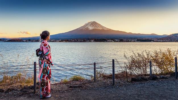 Asian kobieta ubrana w tradycyjne japońskie kimono na górze fuji. zachód słońca nad jeziorem kawaguchiko w japonii.
