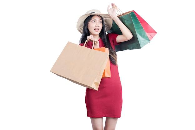 Asian kobieta w kapeluszu prowadzenia torby na zakupy samodzielnie na białym tle