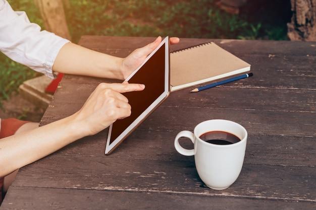 Asian kobieta za pomocą tabletu na stole w kawiarni z rocznika stonowanych.