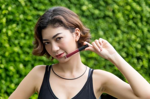 Asian lady pokaż szminki na tle parku